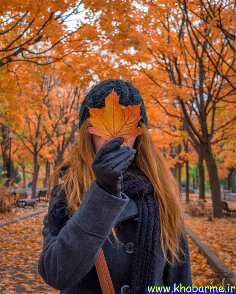 a girl with a leaf in orange autumn fall